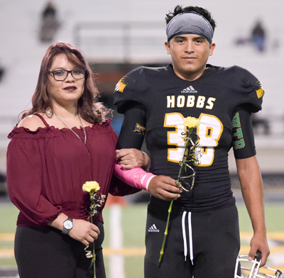 football player standing with mom
