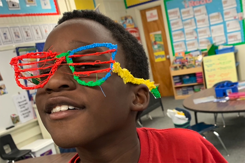 kid posing with glasses made from playdo