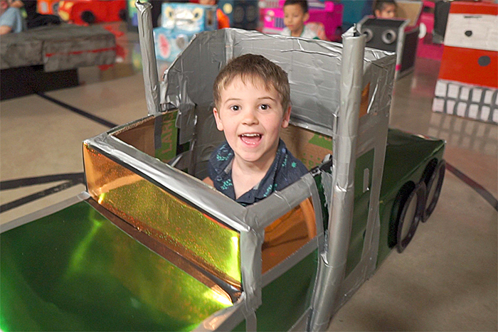 smiling kid in cardboard box that looks like a truck