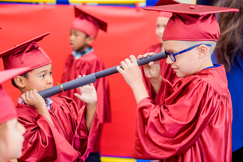 kids in red robes and mortar boards looking through diplomas